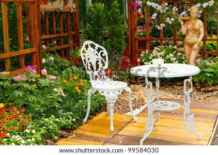 beautiful garden with white tea table and chair - stock photo