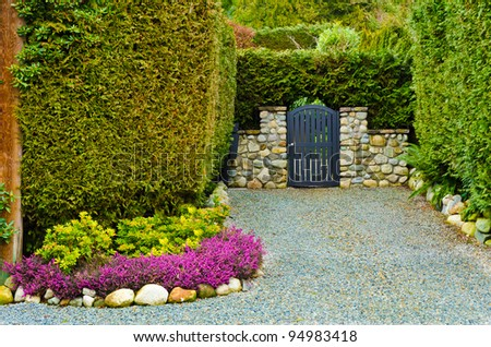 Beautiful gate over fantastic outdoor landscape with stone wall in Vancouver, Canada. - stock photo