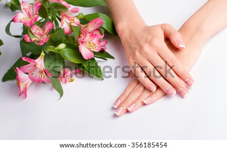 Beautiful gentle moon french manicure with pink flowers on a white background.