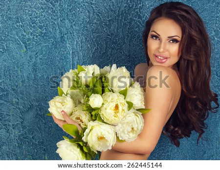 Beautiful gentle slim sexy smiling brunette woman naked with bunch of flowers on blue background with copy space. Spa beauty and healthy life concept - stock photo
