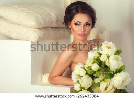 Beautiful gentle slim sexy thoughtful brunette lady sitting naked with bunch of flowers in bright interior background with copy space. Spa beauty and healthy life concept - stock photo