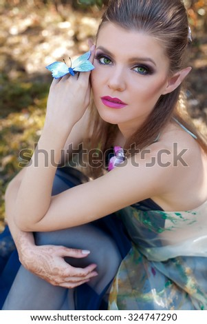 beautiful gentle sweet girl in the fairy tale character in the role of wood elf walking through the forest with butterflies in her hair and on the hand in a long dress with bright makeup and long ears - stock photo