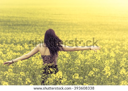 Beautiful genuine woman in sunny summer meadow from behind left. Attractive authentic young girl enjoying the warm summer sun in a wide green and yellow meadow. Part of series. - stock photo