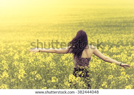 Beautiful genuine woman in sunny summer meadow from behind right. Attractive authentic young girl enjoying the warm summer sun in a wide green and yellow meadow. Part of series. - stock photo