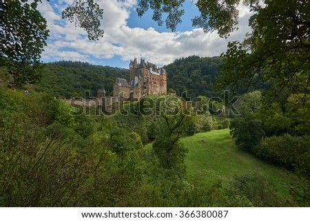 beautiful german medieval castle Eltz Castle or Burg Eltz in the middle of green forest on a sunny summer day panoramic side view.