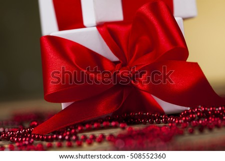 Beautiful gift box with red ribbon on Christmas background