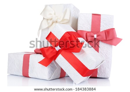 Beautiful gifts with red ribbons, isolated on white - stock photo