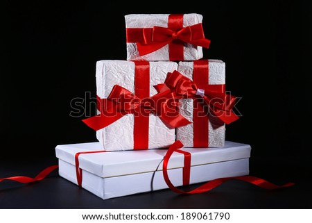 Beautiful gifts with red ribbons, on dark background - stock photo