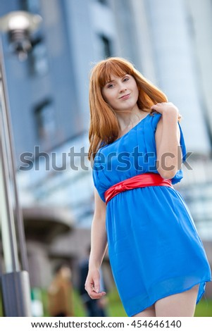 Beautiful ginger-haired woman in blue dress walking outdoors - stock photo