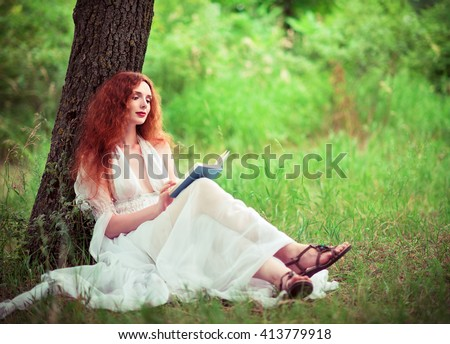 Beautiful ginger woman sitting under the tree and reading a book - stock photo