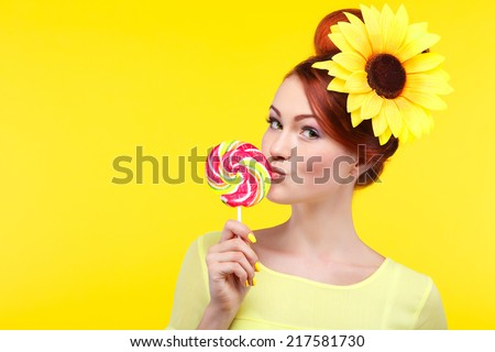 Beautiful gir with a large candyl, isolated on a yellow background with yellow flower in hairs, emotions, cosmetics - stock photo