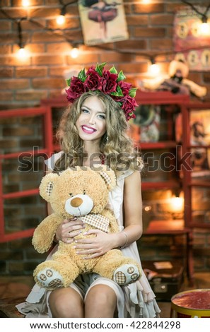 Beautiful girl acrobat, magician's assistant, holding a teddy bear, behind the scenes of the circus arena - stock photo