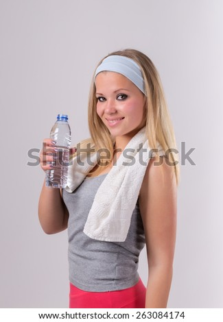 Beautiful girl after fitness with a water bottle. With a towel and a smile. - stock photo
