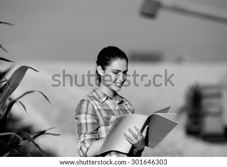 Beautiful girl agronomist with note book standing in  wheat field, combine harvesting in background, black and white image