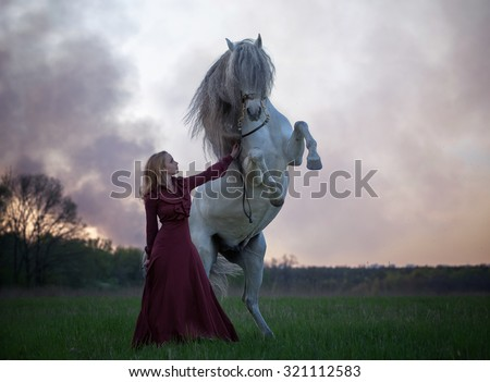 Beautiful girl and Andalusian stallion prancing at sunset