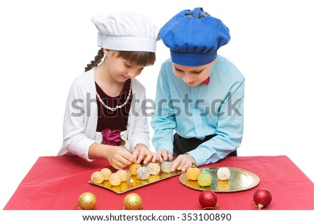 Beautiful girl and boy cooking christmas dessert. Isolated over white background. Copy space. - stock photo