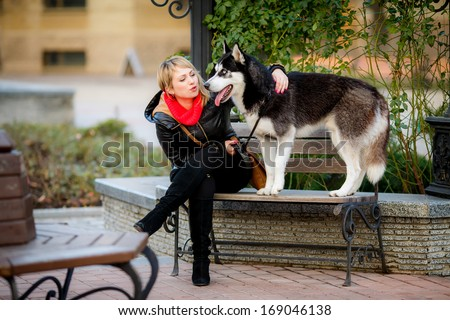 beautiful girl and dog Huskies walking around the city, - stock photo