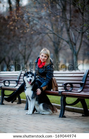 beautiful girl and dog Huskies walking around the city, the owner of the dog sitting on the bench - stock photo