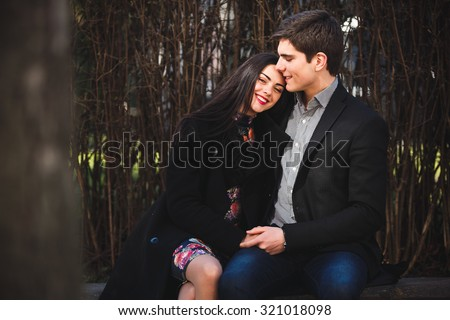 beautiful girl and her boyfriend resting together on a bench in the park - stock photo