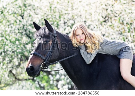 Beautiful girl and horse in blossoming spring garden