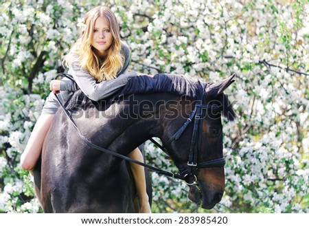Beautiful girl and horse in spring garden - stock photo