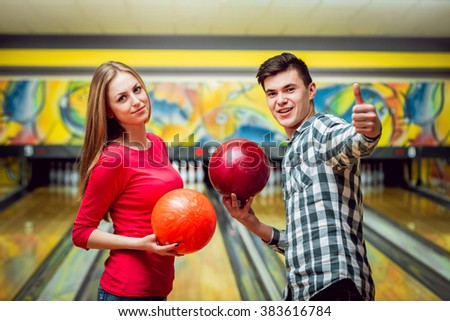 Beautiful girl and young man at the bowling alley with the ball - stock photo