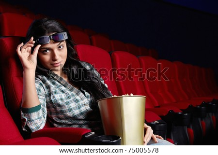 Beautiful girl at a cinema looking at the camera from the 3D glasses