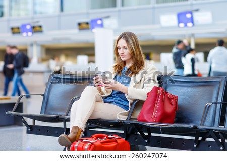 Beautiful girl at international airport, reading her ebook computer and drinking coffee to go while waiting for her flight. Female passenger at terminal, indoors. Traveling people - stock photo