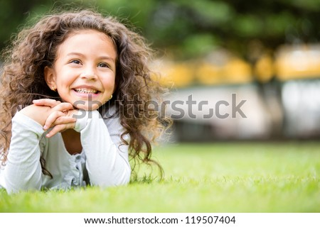 Beautiful girl at the park looking very happy - stock photo