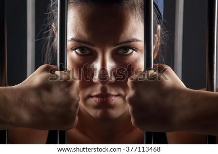beautiful girl behind bars in jail - stock photo