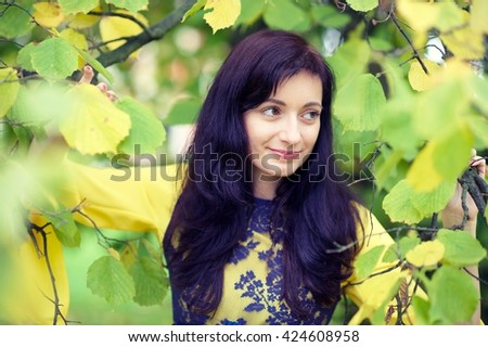Beautiful girl between green and yellow leaves