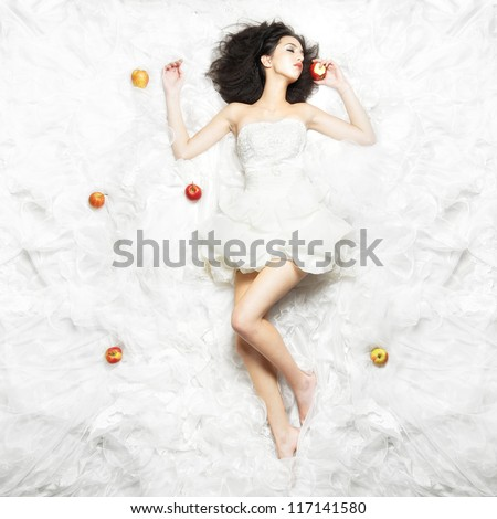 Beautiful girl bites apple and sleeps on a bed of white fabric - stock photo