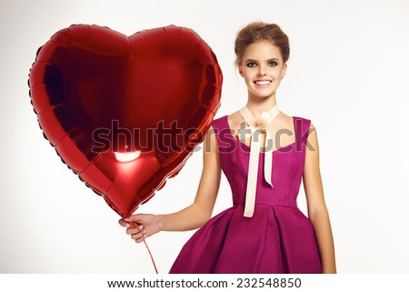 Beautiful girl blonde hair gathered in a bun, evening natural makeup wearing a bright pink short evening dress and elegant high heels holding a big red balloon in the form of hearts, Valentine's Day. - stock photo
