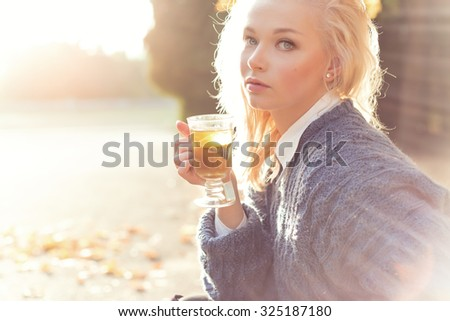 beautiful girl blonde in warm sweater drinking tea in the Park on a Sunny autumn day in the bright rays of the sun - stock photo