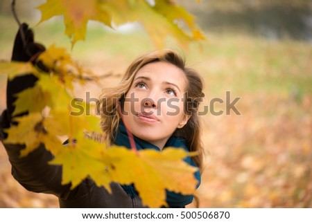 Beautiful girl blonde with wavy hair wearing a blue scarf standing at autumn tree with yellow leaves