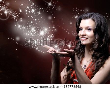 beautiful girl blowing magic stars - stock photo