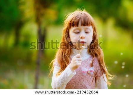 beautiful girl blowing on white dandelion - stock photo