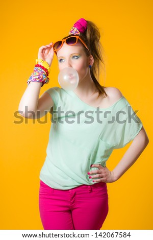 Beautiful girl blows bubble gum ball, yellow background