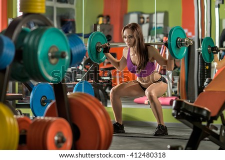 beautiful girl bodybuilder,  execute exercise squatting with  weight, in gym - stock photo