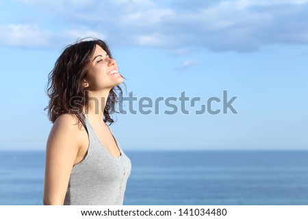 Beautiful girl breathing and smiling on the beach with the sea and blue sky in the background - stock photo