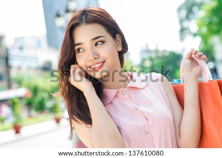 Beautiful girl carrying her purchases and making a phone call - stock photo