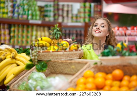 Beautiful girl chooses fruit at the grocery store - stock photo