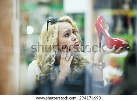 beautiful girl chooses shoes in a shoe store - stock photo