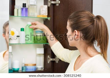 Beautiful girl choosing beauty products from the bathroom cabinet - stock photo