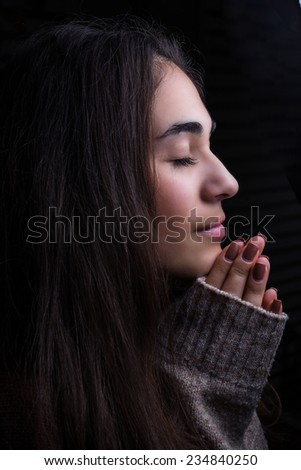 Beautiful girl clasped her hands in prayer and praying for Paris
