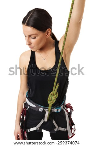 Beautiful girl climber makes the safety knot before climb. Fully equipped for rock climbing, extreme sport Isolated on white background. - stock photo