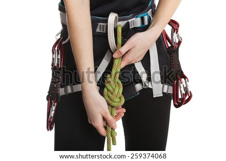 Beautiful girl climber show how to make the safety knot before climb. Fully equipped for rock climbing, extreme sport. Isolated on white background. - stock photo
