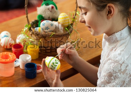 beautiful girl colored Easter eggs sitting at the table - stock photo