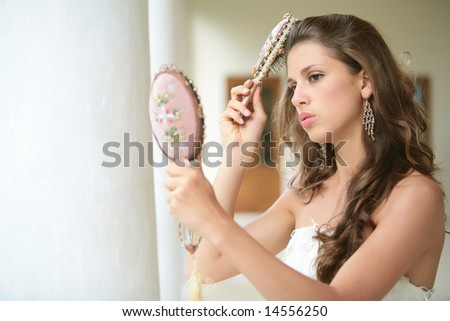 beautiful girl combs luxurious dark hairs, does hairstyle, horizontal portrait - stock photo