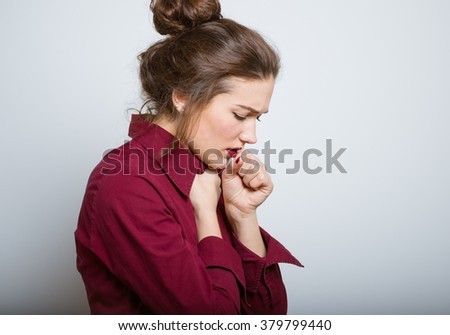 Beautiful girl coughing isolated on a gray background - stock photo